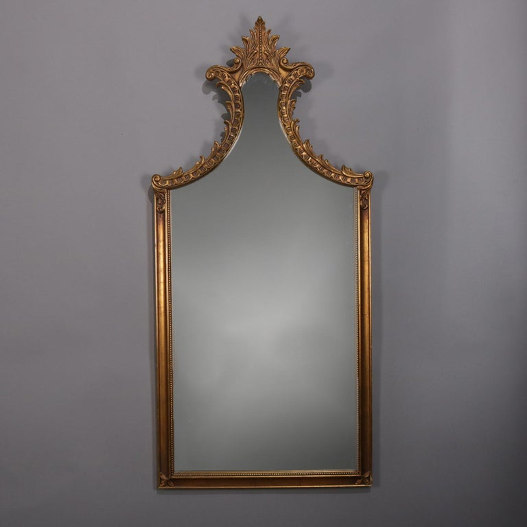 Large French Louis XV style wall mirror features shaped form with foliate and scroll decorated giltwood frame surmounted by an acanthus form crest, circa 1930  ***DELIVERY NOTICE – Due to COVID-19 we are employing NO-CONTACT PRACTICES in the