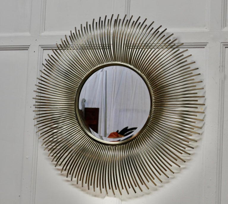 Large French midcentury sunburst-starburst steel mirror  A great piece, the large starburst or sunburst radiates out from the central beveled mirror, the rays are made in delightfully curved tubular steel A Classic from the era, a very large