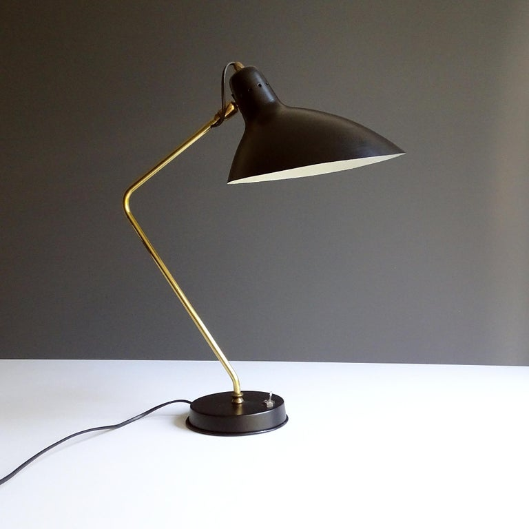 Mid Century Desk lamp by Jean Boris Lacroix, circa 1955-1960 with its signature elongated shade and bend brass stem, extremely rare early version with aircraft type switch.  Wiring: The lamps have been tested with US American light bulbs under 120v