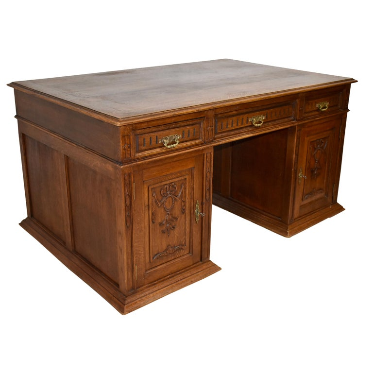 Beautiful from every angle, this oak partner's desk is comprised of a rectangular top and two pedestals. The top features a beveled edge, sharp corners, and three drawers on one side with matching faux drawers on the opposite side. The pedestals