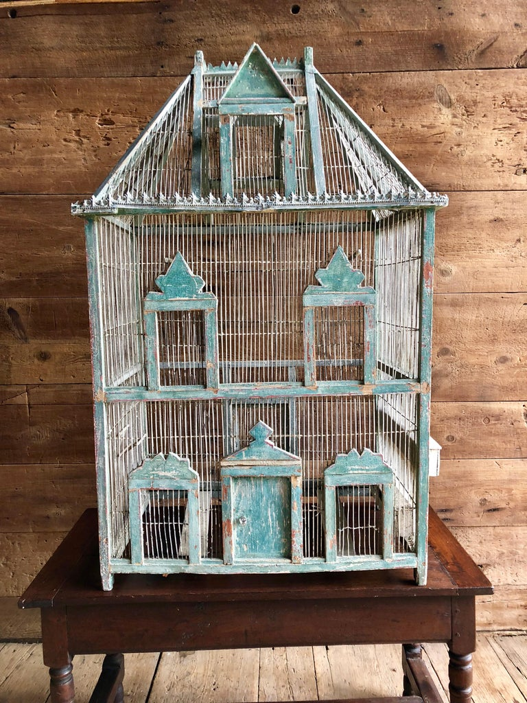 A large French painted birdcage in wire and wood in the form of a chateau, with original blue or green painted finish and embossed tin trim, 19th century.