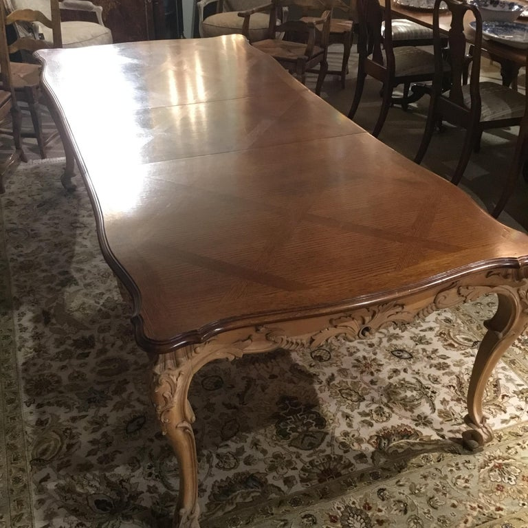 """Handsome and long dining table with carved apron in a light pine finish. The top is made of Walnut in a parquetry inlay pattern in a darker finish. This table has two leaves that extend this table to a total Length of 116"""". This table has two"""