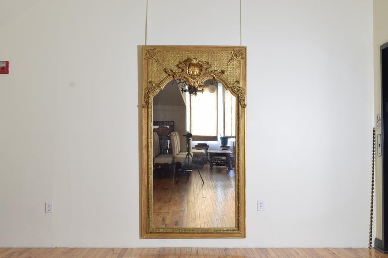 Covered entirely in 23.5 karat gold which has a slightly darker hue than 24 karat gold which appears slightly more red, this mirror incorporates elements of the French Regence period with its criss-crossed lozenge form design in the upper section