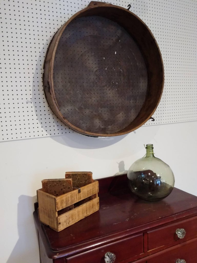 If you are looking for a large piece to hang on the walls of your country home your ship has arrived. The rim is wood and a bit warped with age and the middle is metal. It dates from 1870. There is a handle on top of the piece and we love this piece