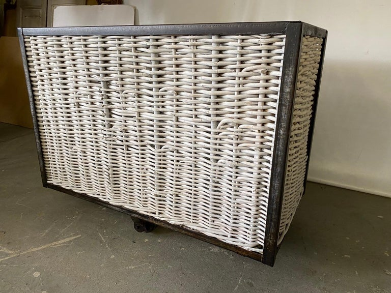 A substantial steel frame and wicker or rattan multipurpose French laundry bin on wheels. The sides and base are made from wicker/rattan. The steel frame is supported by large metal castors for easy movement. This was once used in either a