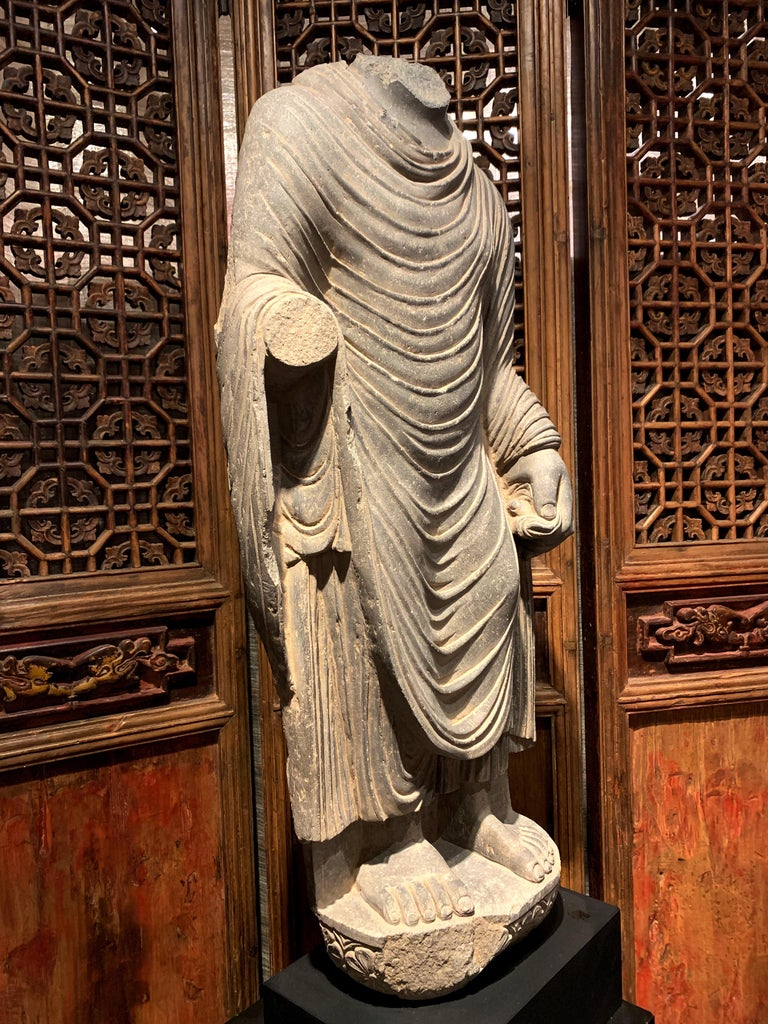 A large and powerfully carved gray schist Gandharan standing Buddha featuring wonderful drapery, ancient region of Gandhara, circa 2nd - 3rd century. Although missing his head and gesturing hand, this figure can still be identified as the historical