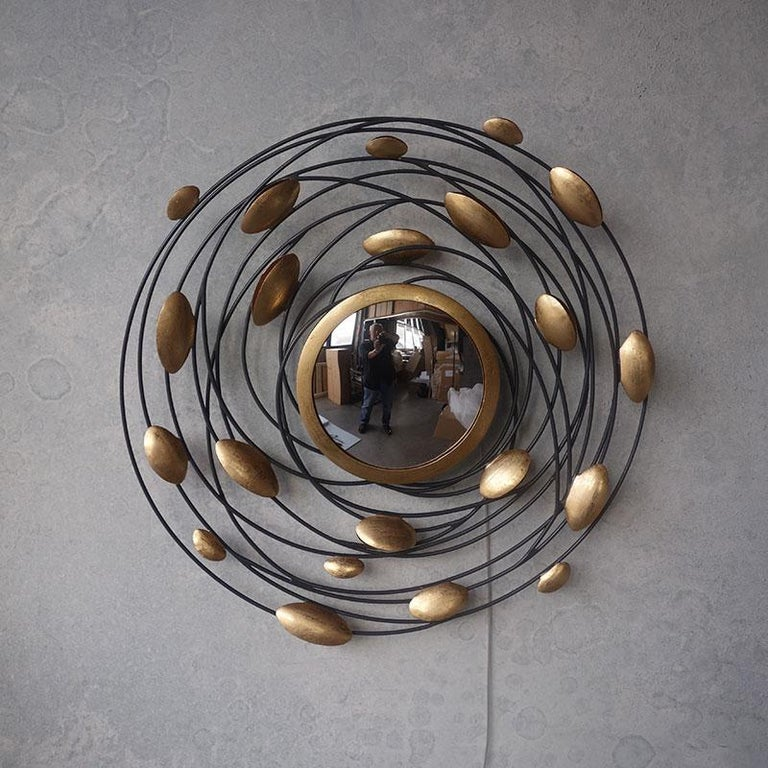 Bright, sparkling and large gilded metal wall light (6 x 10 watt), just as a sculpture, precious and high quality composed of a round, organic and aerial metal structure in gold finish and adorned with a round mirror. Amazing!