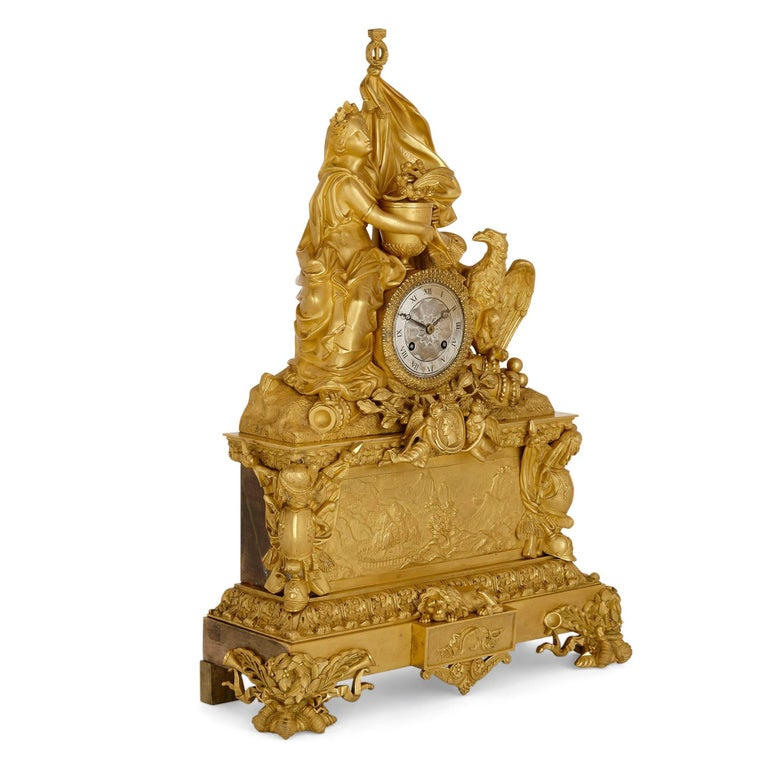 Large gilt bronze mantel clock commemorating Napoleon French, circa 1840 Measures: Height 57cm, width 40cm, depth 15cm  The gilt bronze mantel clock is set on a rectangular, tiered base with four decorative feet. The lower tier is centered with