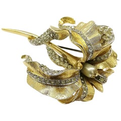Large gilt metal, clear paste 'orchid' brooch, Marcel Boucher, 1960s, USA.