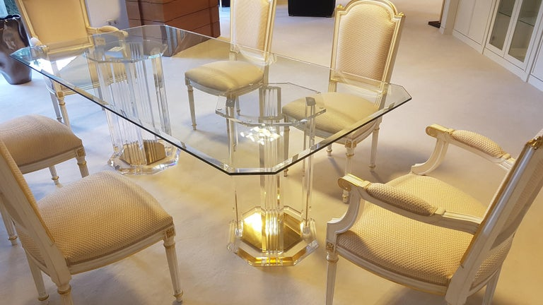 Stunning dining room set consisting of a six seating dining table made of plexiglass and cut glass and wooden chairs with a luxurious matt white and gold color combination. The dining table features two large plexiglass central columns which hold
