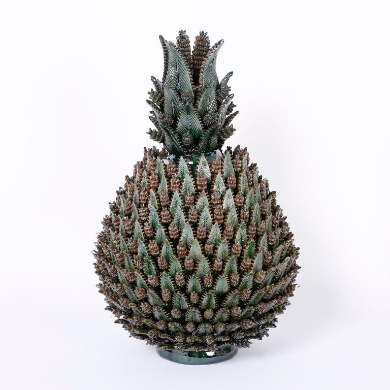 Here we have an amazing display of pottery brilliance in the form of this pair of glazed terra cotta stylized pineapples with an ambitious composition of leaves and cones in a varigated green glaze. One of a kind custom designed for F. S. Henemader.