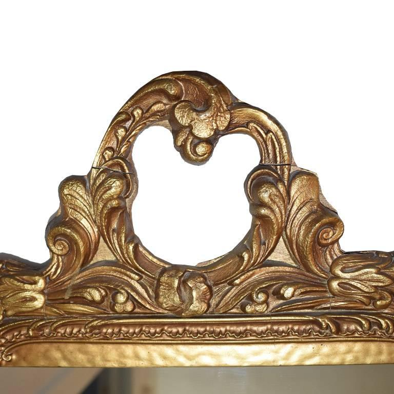 Large rectangular giltwood mirror. In a wide rectangular shape, with hand-carved details on top. Wear is consistent with age. Gorgeous over a mantel, or as an addition to a wall of mirrors.