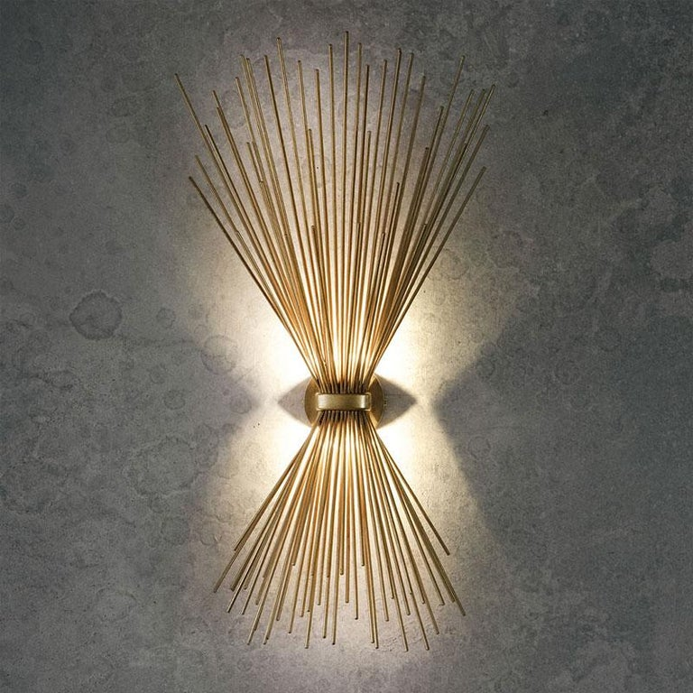 Bright, sparkling and large Metal Art Deco style wall light, precious and high quality composed of an aerial metal structure in gold leaf finish.