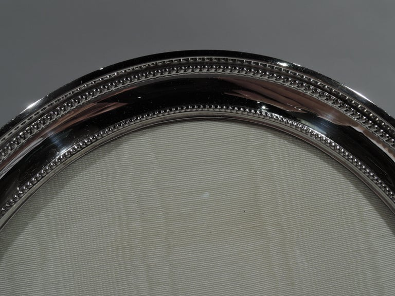 Large sterling silver picture frame. Made by Gorham in Providence, circa 1920. Oval window and concave surrounded with beaded borders. Two ball supports. With glass, silk lining, and velvet back and hinged support. For portrait (vertical) display.
