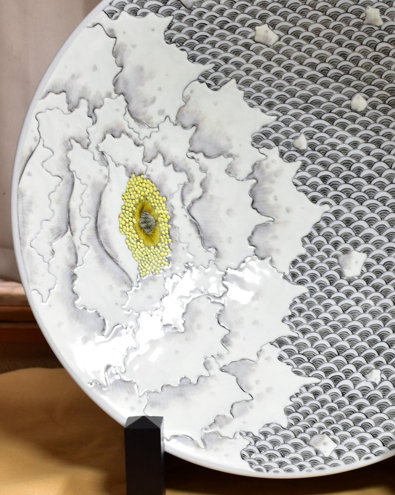 Mesmerizing Japanese contemporary decorative porcelain deep charger/centerpiece, hand painted in cream and various shades of gray. It is a masterpiece by this Kutani master artist whose signature bald flowers create a breathtaking scene. The