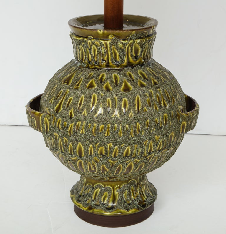 The large bulbous form with a hand notched surface and glazed in tones of light green.