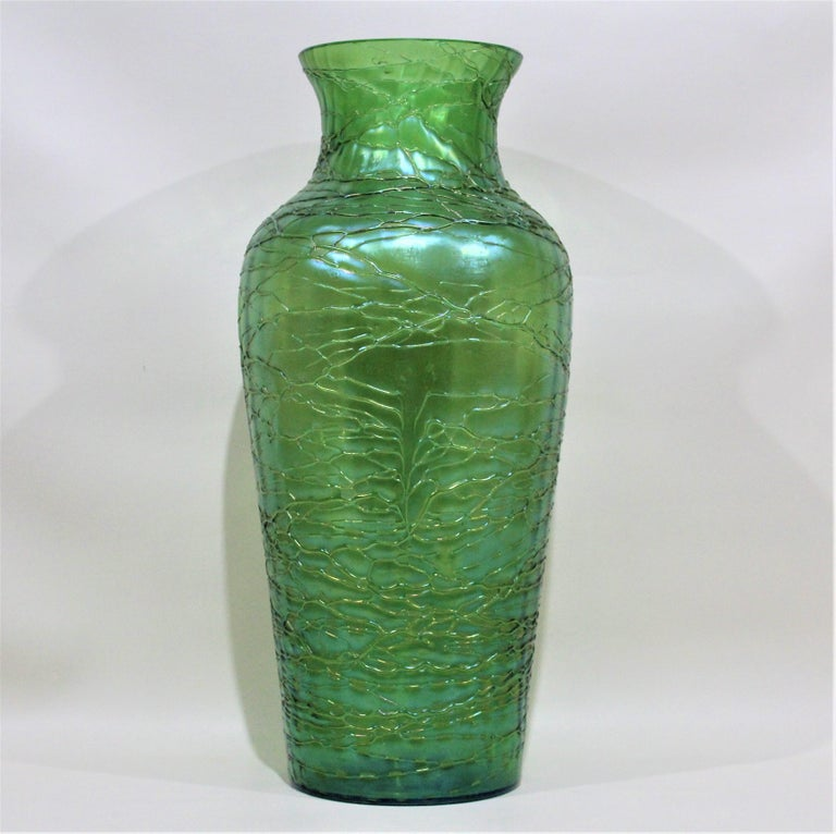 This substantial iridescent deep green vase was made by Loetz in and around the Early 20th century in an Arts & Crafts or Art Nouveau style. The entire vase is artfully decorated with hand applied threading in the same color, and accentuates the