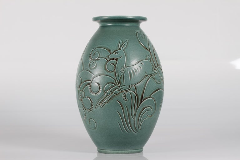 This huge Danish ceramic floor vase is designed by Aksel Sigvald Nielsen (1910-1989) signed as AKSINI, and made by Knabstrup ceramic in the middle of the 20th century.  The vase has a green satin glaze and a young deer and plant ornaments as a