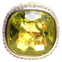 Large green stone surounded by CZ in a Gold coloured band