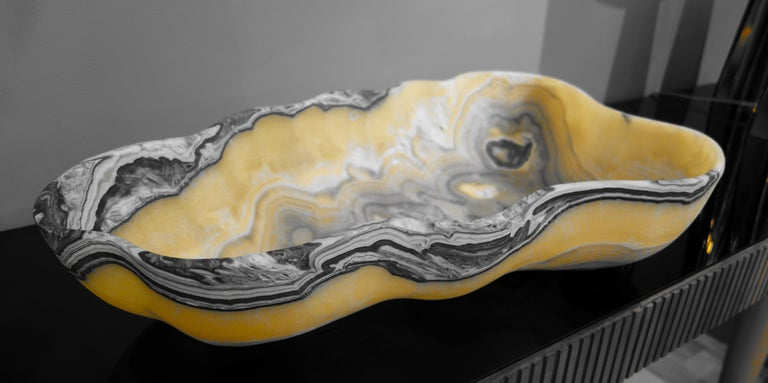 A very large hand carved Mexican onyx bowl or centerpiece in striking striations of gold, charcoal gray and white with natural negative spaces.