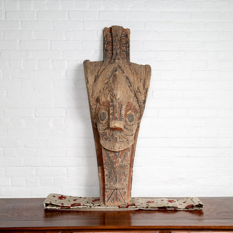 A large antique hand carved tribal carving from the Batak people, northern Sumatra, called a Singa Singa. Attracting our eye with its charismatic presence, this large hand carved sculpture from the Indonesian island of Sumatra is one of the most