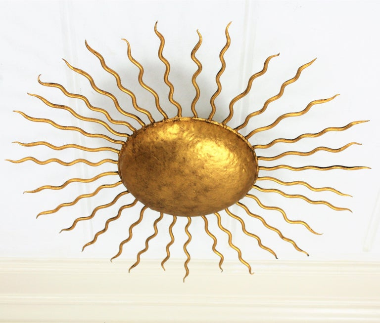Beautiful hand-hammered gilt iron sunburst light fixture with Brutalist accents. Richly decorated with hand-hammered marks. It has curly iron rays in two sizes surrounding the central sphere. It can be placed as ceiling light fixture but also as a