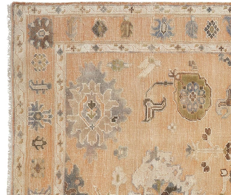 A large room sized rug with design in style of Oushak. This beautiful rug was handmade using two different styles. The background is flat-woven Kilim and the motives are hand knotted. This results a special rustic look. The light salmon color is