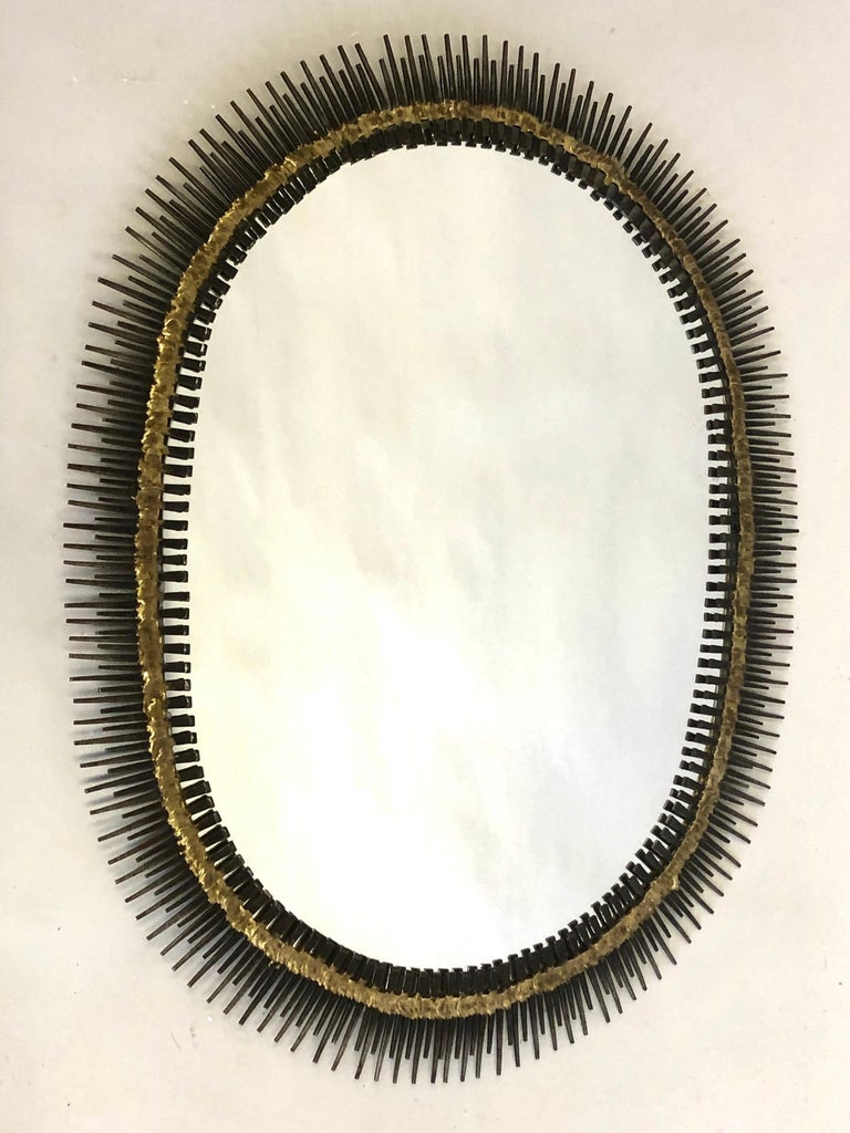 Elegant handmade midcentury wall mirror or wall mounted sculpture in a chic oval sunburst form by the French Canadian artist, Bela composed of steel nail heads soldered together by solid brass to form a dynamic Brutalist composition.  Central