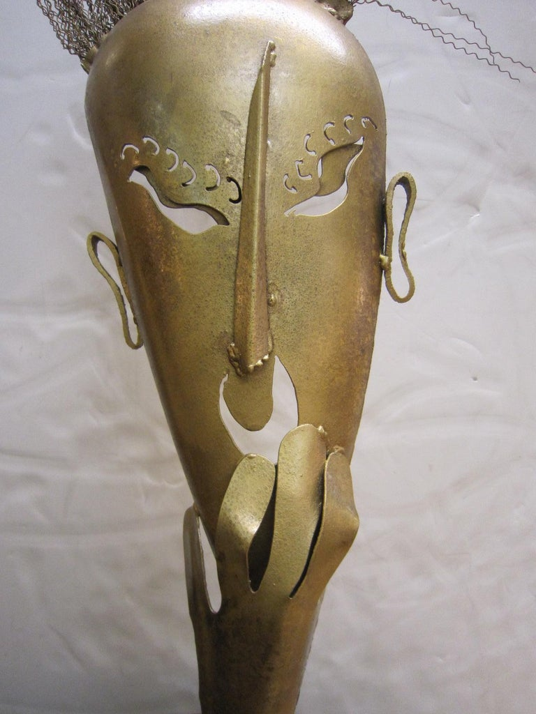 A large steel statue of a hand cut figural mask with lively wire hair in a mottled dark antique gold / brass painted finish with a slightly textured surface. Wiener Werkstatte, Hagenauer style with decorative eyelashes, exotic shaped eye cut-outs,