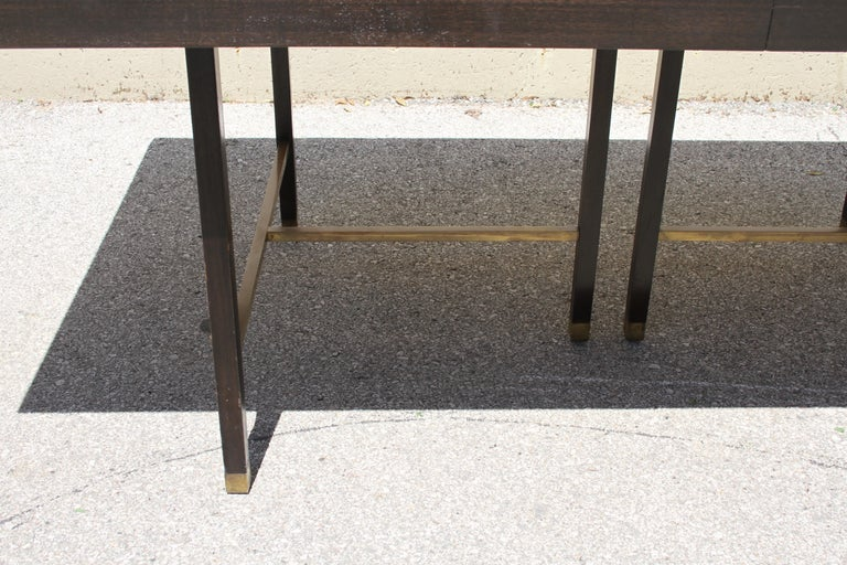Classic Mid-Century Modern Harvey Probber mahogany dining table with heavy brass cross stretchers and sabots, includes two 16.5