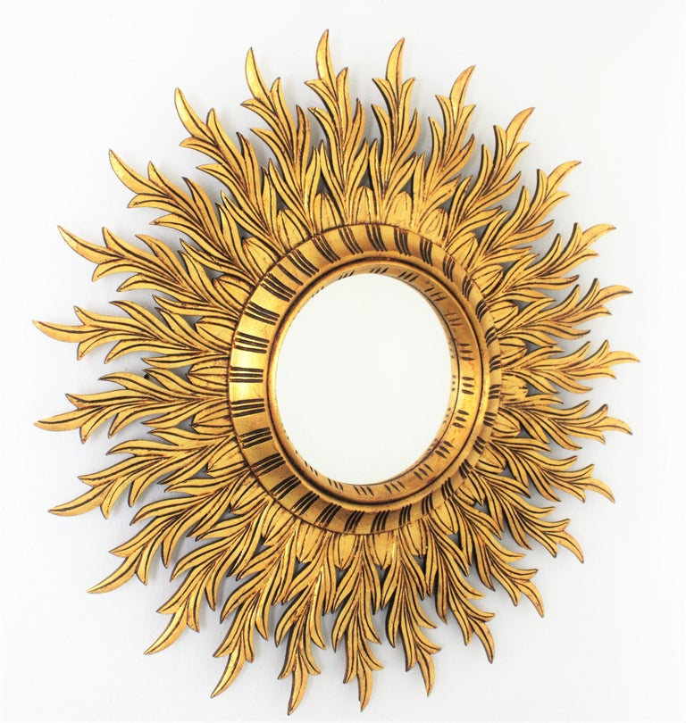 An amazing finely carved giltwood sunburst mirror with gold leaf finish in the style of Hollywood Regency.