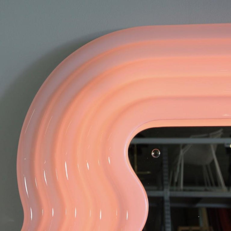Ultrafragola mirror, designed by Ettore Sottsass. Italy, 1970.  Recent production mirror made of moulded fibreglass with wooden back and shaped mirror. The frame is white, turning pink when neon light is switched on.
