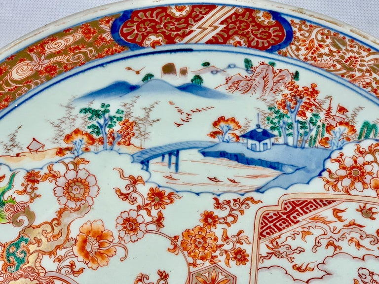 Large finely decorated Japanese Meiji period  Imari porcelain charger. The decoration consists of shaped panels overlayed on floral sprays. The stylized border has cloud forms on a fret work background. The enamel colors have a cobalt blue
