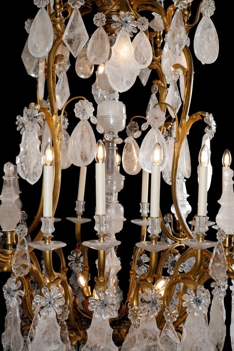 Of cartouche outline, with rock crystal baluster shaft with acanthus scroll branches of light and spires, hung with large rock crystal plaques, faceted drops, rosettes obelisks all from rock crystal, terminating with a faceted solid rock crystal