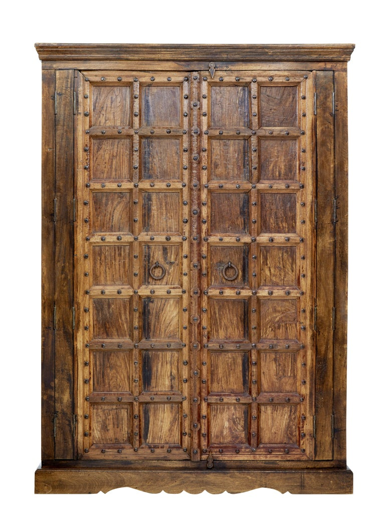 Beautiful imposing hardwood wardrobe circa 1950.  With doors dating from the early 19th century this creates this feature piece.  Heavy panelled doors with metal stud work and handles, opens to a two thirds hanging rail space and a 1 third space