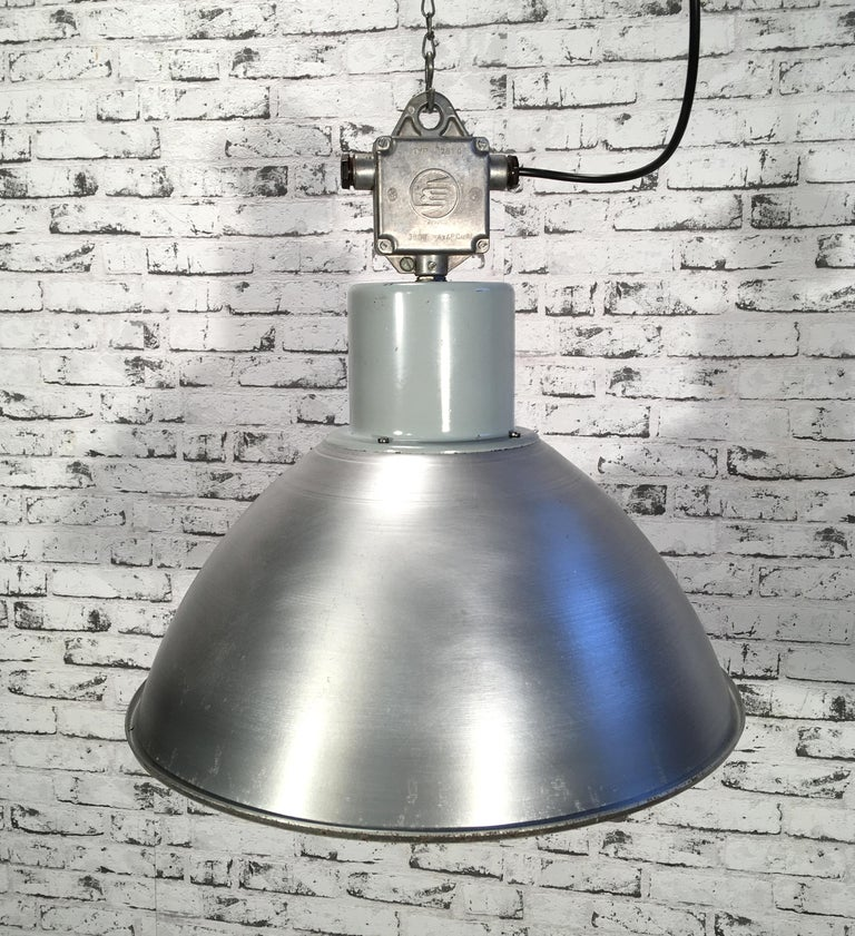 This pendant lamp was originally used in a factory in former Czechoslovakia in the 1960s. The piece is comprised of an aluminum lampshade and a cast aluminum top. The lamp is fully functional and features a new porcelain E27-socket and wire. The