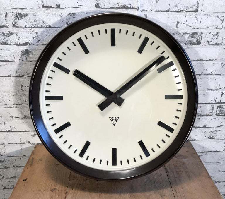 This large wall clock was produced by Pragotron in former Czechoslovakia during the 1960s.It features a brown bakelite frame, white plastic dial, aluminium hands and clear glass cover. The piece has been converted into a battery-powered clockwork