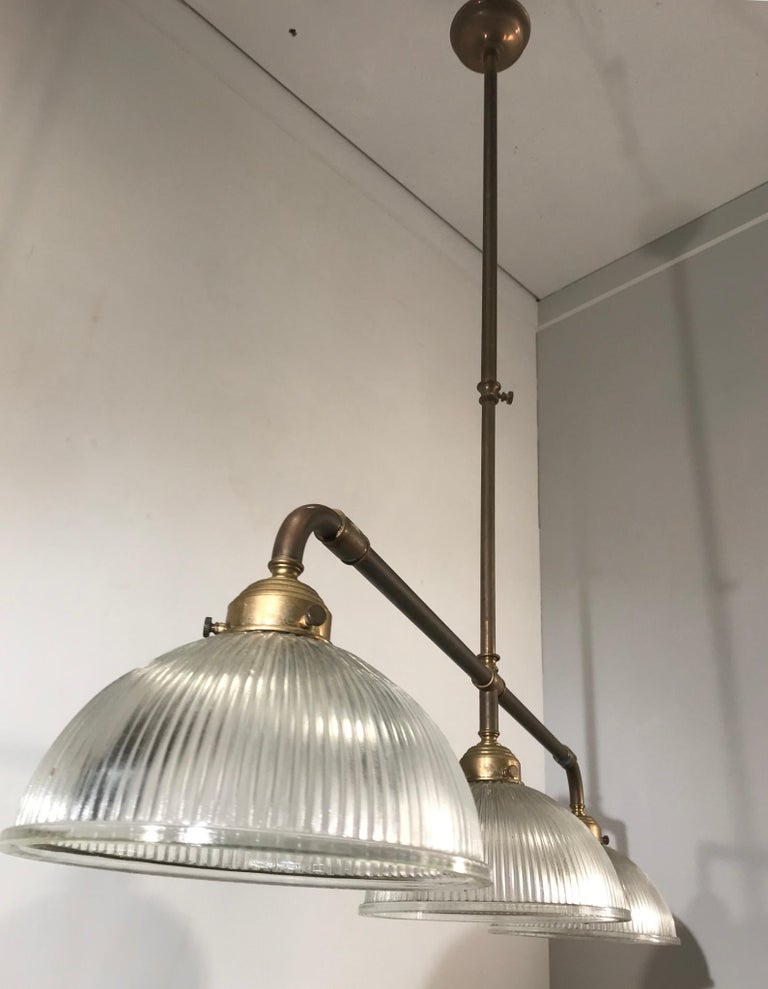 Patinated Large Industrial Three-Light Holophane Glass Style Chandelier with Brass Rods For Sale