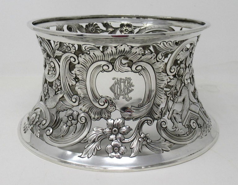 An exquisite Irish Georgian style Dublin silver heavy gauge table dish ring of traditional waisted form and unusually large size.  The circular inverted sided lavish pierced body depicting birds in flight, a shepherd, fisherman and a peasant in