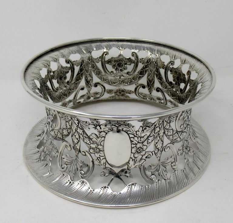 An exquisite Georgian style sterling silver English heavy Gauge table dish ring of traditional waisted form and unusually large size.   The circular inverted sided lavish pierced body depicting chased garlands and swags with flowers. The central