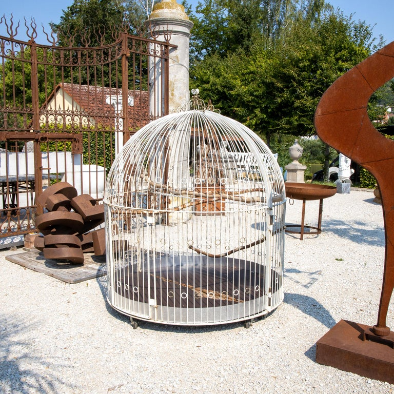 Large birdcage or aviary made of white-painted iron bars with ring elements and crowning floral decoration. The cage stands on wheels and can be divided in the middle.