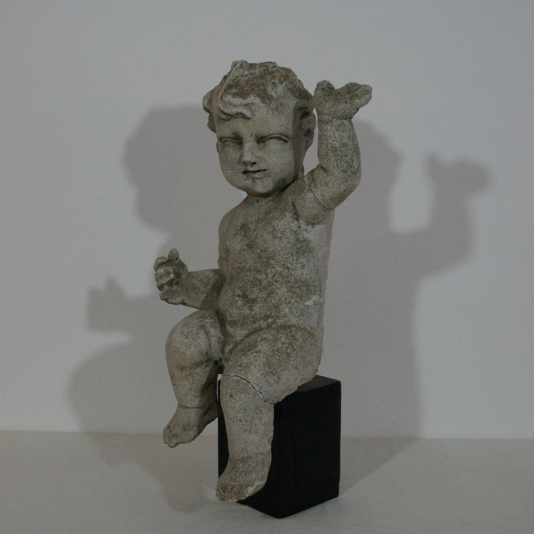 Great and unique find. Hand carved stone baroque cherub. Italy, circa 1750. Weathered, old repairs and small losses. Measurement with the base.