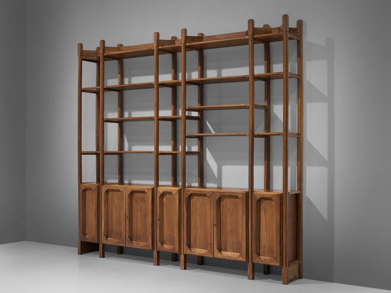Bookcase, walnut, brass, Italy, 1960s  Wonderful Italian open bookcase with five cabinets. All elements feature carved details that contribute to the sculptural and grand expression of the shelf. Five columns in two widths all start with a cabinet