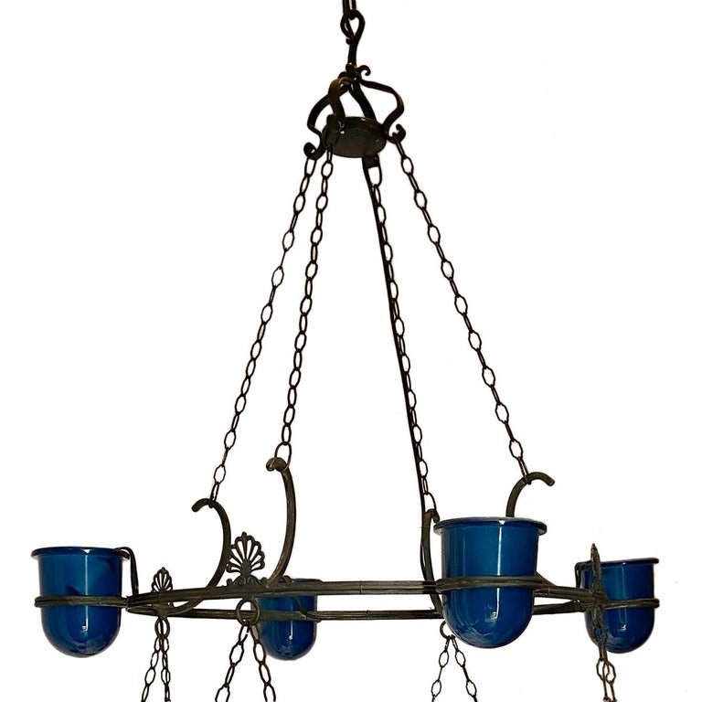 A large circa 1900s sixteen light patinated and cast bronze Venetian chandelier with aqua blue glass insets.