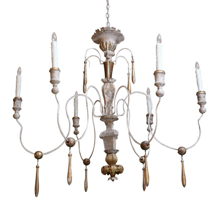 Large Italian chandelier from antique elements with six later iron arms. All wooden parts are hand carved 18th and 19th century fragments adorned with remnants of original gilt finish. Newly wired for use within the USA using all UL listed parts.