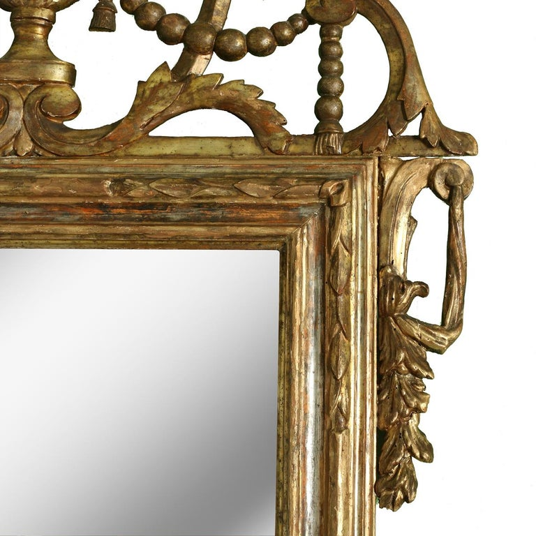 Large Italian giltwood antique mirror, rectangular in shape, with urn form and garland, leaf and floral details.