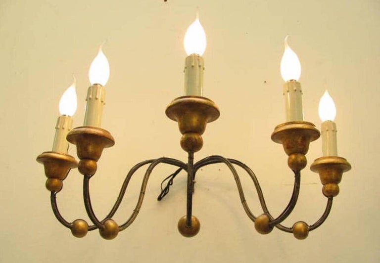 A large five-arm Italian sconce, five curved iron curved arms decorated with gilded walnut balls and ending with turned gilded walnut bobeches and candles arranged for Edison 14 bulbs.   Working wiring for Italian standards, it comes from a private