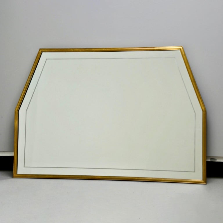 """Circa 1960s Italian mirror has a narrow brass frame and six sided trapezoidal shape. Mirror itself has an etched border. Unknown maker.   Actual Mirror Size:  33.5"""" h x 50"""" w"""
