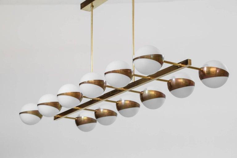 Beautiful modern chandelier Stilnovo style, structure in brass with opaline light. 12 big exterior globe. Diameter opaline 14 cm. Bulb E14.