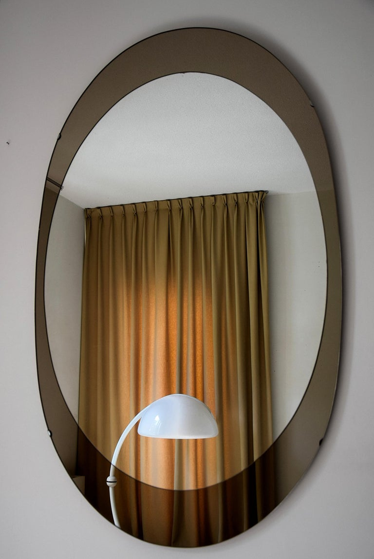 Impressive and stylish oval mirror with stylish bronze mirrored frame produced by Cristal Arte, Italy in the 1960s. This beauty measures 132 cm or 4.4 feet x 80 cm or 2.8 feet. It can be hung either vertical or horizontal as can be seen in the